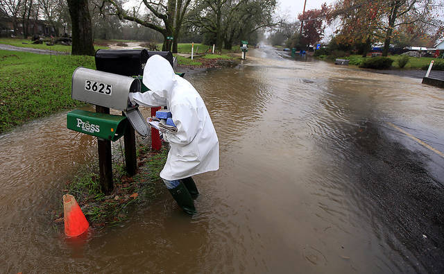 Sandy LeDuc braves floodwaters to gather her mail on Piner Road, Friday Dec. 21, 2012 in Santa Rosa, Calif as a large winter storm barreled in to Northern California. (AP Photo/The Press Democrat, Kent Porter)