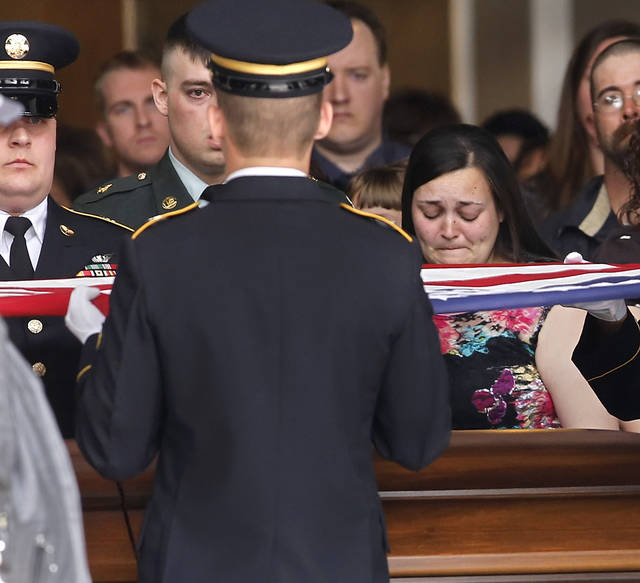 Grief can be seen on the face of Miranda Whipple as a military honor guard slowly and precisely fold the American flag that once draped the casket of her brother-in-law, Rex Schad.  Schad's brother, US Army Spc. Max Whipple can be partially seen, his eyes staring into the eyes of the soldier holding the flag above his brother's casket. Celebration of Life service  for US Army SSgt. Rex L. Schad at LifeChurch.tv in Edmond Thursday afternoon,  March 21, 2013.  Schad was killed earlier this month while conducting a patrol brief with the Afghanistan National Police.  He is a 2005 graduate of Edmond Memorial High School.    Photo by Jim Beckel, The Oklahoman