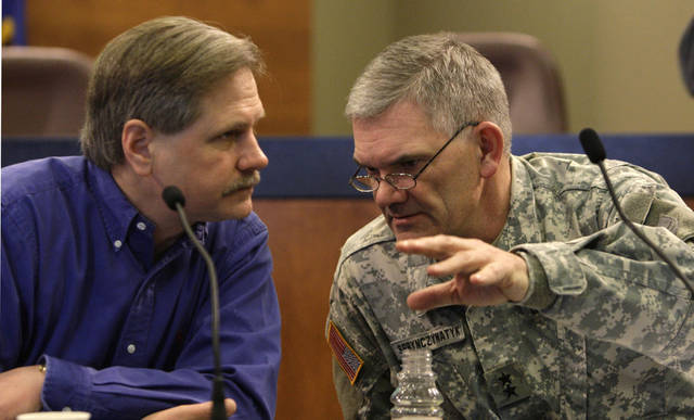 North Dakota Gov. John Hoeven, left, talks with National Guard Maj. Gen. David Sprynczynatyk during a public briefing on flooding there Sunday, March 29, 2009, in Fargo, N.D. The Red River apparently crested Saturday, forecasters said, leaving residents to wearily hope their sandbag-fortified dikes continue to hold back record-setting floodwaters. (AP Photo/Elaine Thompson)