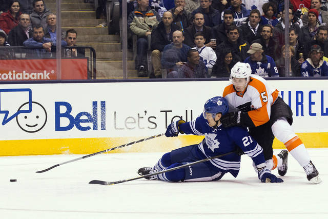 Toronto Maple Leafs' James van Riemsdyk (21) battles for the puck with Philadelphia Flyers' Braydon Coburn during the second period of their NHL hockey game, Monday, Feb. 11, 2013, in Toronto. (AP Photo/The Canadian Press, Chris Young)