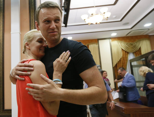 Russian opposition leader Alexei Navalny, right, embraces his wife Yulia, as he was released in a courtroom in Kirov, Russia on Friday, July 19, 2013.A Russian court on Friday released opposition leader Alexei Navalny from custody less than 24 hours after he was convicted of embezzlement and sentenced to five years in prison.The release came after a surprise request by prosecutors, who said that because Navalny is a candidate in this fall's Moscow mayoral race keeping him in custody would deny him his right to seek election. (AP Photo/Dmitry Lovetsky)