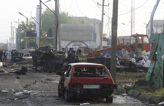 A police officer using a mobile phone takes a picture as others examine the site of a powerful explosion on the outskirts of Makhachkala, southern Russia, Friday, May 4, 2012. Two powerful explosions went off Thursday night near a traffic police post in the capital of Russia's restive Dagestan region. (AP Photo/Abdula Magomedov, NewsTeam)