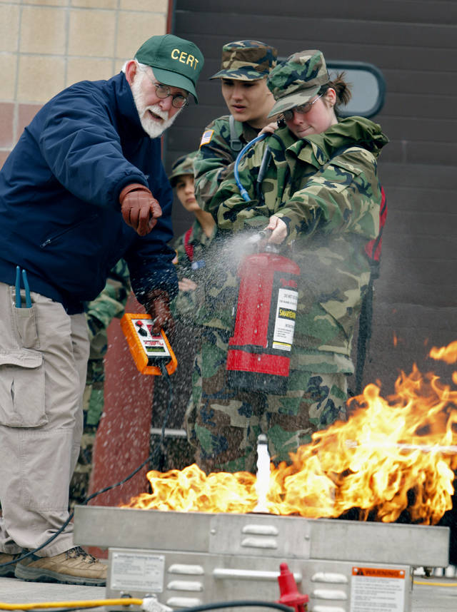 Civil Air Patrol cadets David Fite, back, of Newalla, and Ashley Hale, right, of Grove, practice fire suppression techniques under the guidance of Charles Woltz during a training exercise Saturday. PHOTO BY STEVE SISNEY, THE OKLAHOMAN