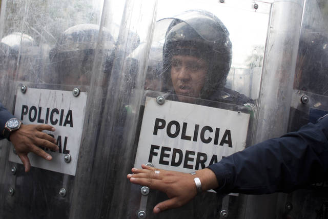 A Mexico's Federal Police officer reacts while watching public school teachers breaking the fence that blocked a street near Mexico's Interior Ministry during a demonstration in Mexico City, Thursday, April 4, 2013. Radical Mexican public school teachers are holding marches and blocking roads to battle a newly enacted education reform that would weaken union powers. (AP Photo/Alexandre Meneghini)