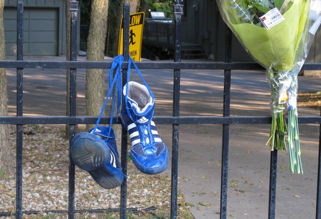 Wrestling shoes and flowers hang from the fence of the home of Ron and Rebecca Bramlage and their four children, left by friends and neighbors, Thursday, June 7, 2012, in Junction City, Kan. The family died in a Florida plane crash, and three Bramlage boys were wrestlers. (AP Photo/John Hanna)