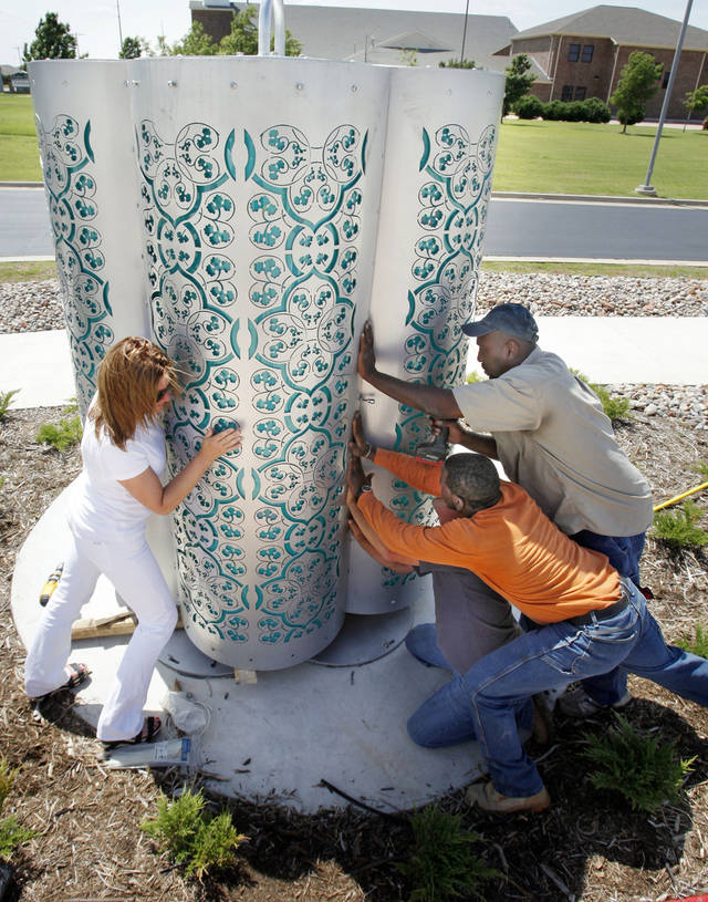 """Artist Deedee Morrison, Birmingham, Ala. (left) installs her kinetic, lighted sculpture """"Borrowed Light"""" with the help of Libra Electric employees Leo Gross (top right) and Eric Jackson, in front of the new Southwest Oklahoma City Library, at  2201 SW 134th Street on Thursday, May 10, 2012, in Oklahoma City, Okla.   Photo by Steve Sisney, The Oklahoman"""