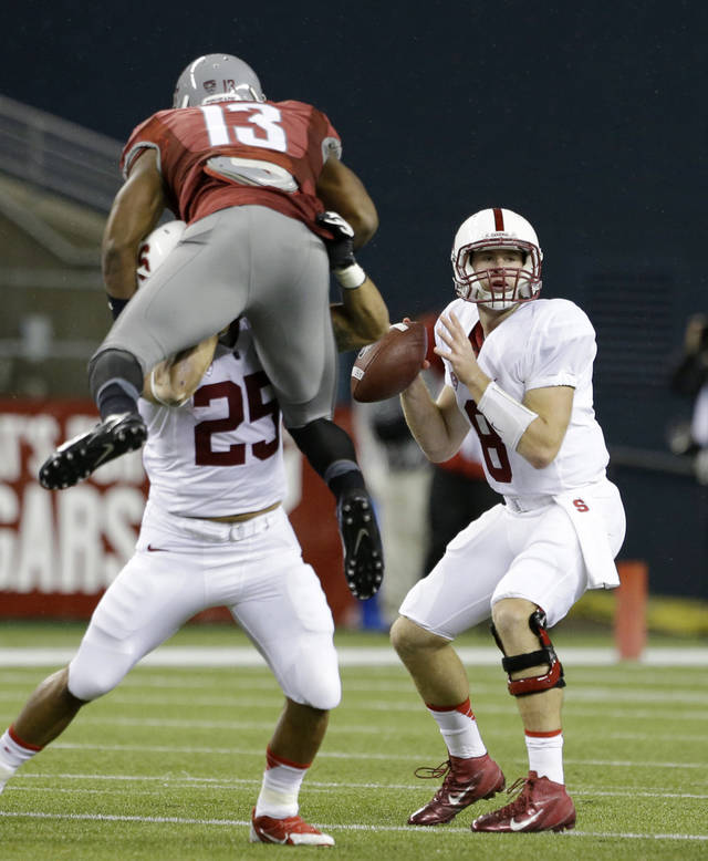 Stanford quarterback Kevin Hogan, right, looks to pass as Alex Carter (25) keeps Washington State's Darryl Monroe away in the first half of an NCAA college football game on Saturday, Sept. 28, 2013, in Seattle. (AP Photo/Elaine Thompson)