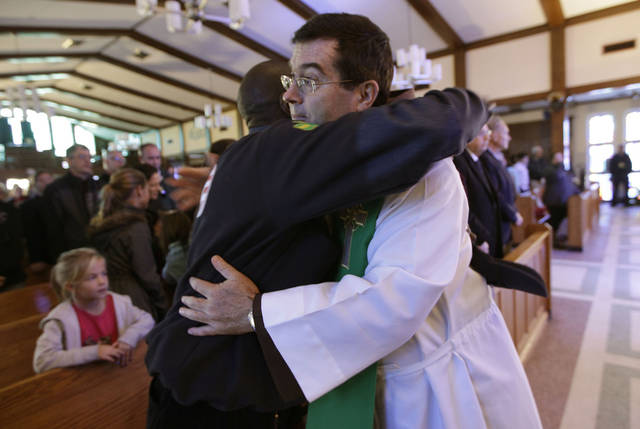 <p>The Rev. Brian Jordan, right, embraces New York State Senator Malcolm Brown after Sunday mass at St. Thomas More Catholic Church in Breezy Point, Sunday, Nov. 4, 2012, in New York. Breezy Point, the beachfront enclave heavy populated by firefighters and police officers was devastated during the storm when a fire pushed by Sandy's raging winds destroyed 100 or more homes and buildings. (AP Photo/Kathy Willens)</p>