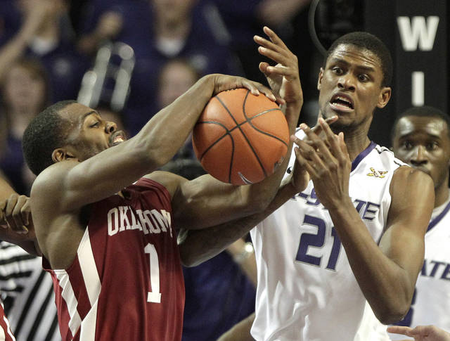 Oklahoma guard Sam Grooms (1) steals the ball from Kansas State center Jordan Henriquez (21) near the end of an NCAA college basketball game on Saturday, Jan. 28, 2012, in Manhattan, Kan. Oklahoma won the game 63-60. (AP Photo/Charlie Riedel) ORG XMIT: KSCR110