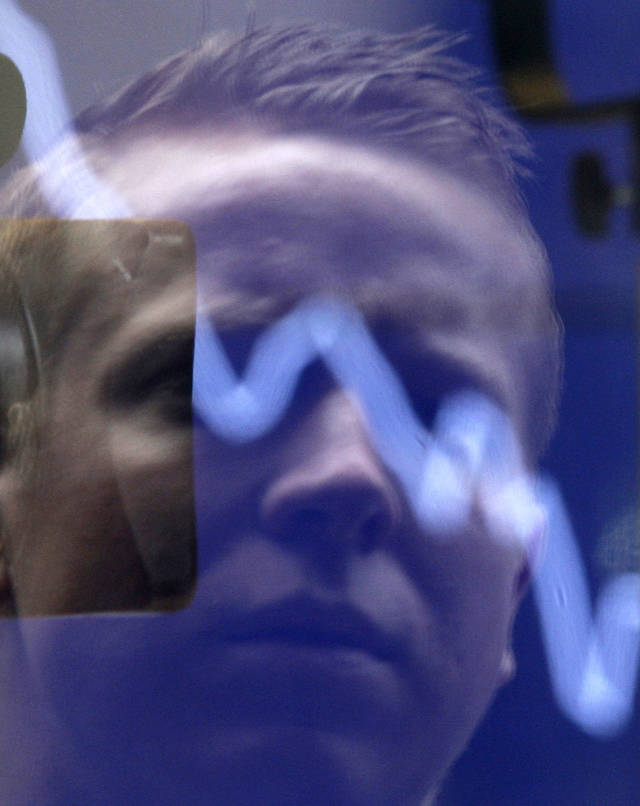 A man watches through a window as the Australian Stock market opens in Sydney, Tuesday, Aug. 9, 2011. The U.S. stock market buckled Monday under the weight of a crisis in Europe and danger of recession at home. (AP Photo/Rick Rycroft)