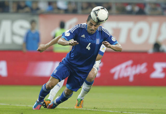 Greece's Nikos Spyropoulos goes for a header during their World Cup Group G qualifying soccer match against Bosnia-Herzegovina, at Karaiskaki stadium, in Piraeus port, near Athens, Friday, Oct. 12, 2012. (AP Photo/Petros Giannakouris)