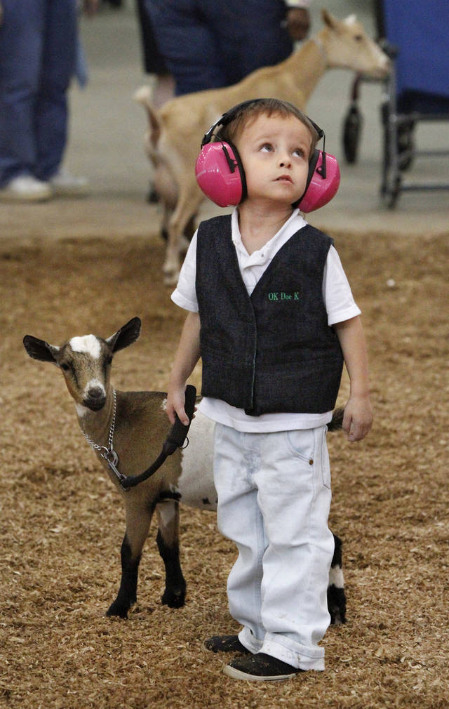Paul Goodchild, 4, of Norman, stands beside Emmy, his Nigerian Dwarf goat after showing her in the three to six month class during goat judging at the Oklahoma State Fair on Wednesday, Sep. 19, 2012. This is Goodchild's first time to show an animal at the state fair. Emmy won a second place ribbon; Paul was awarded a first place ribbon for showmanship.  Photo by Jim Beckel, The Oklahoman.