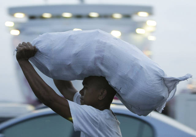 A member of the Philippine Coast Guard carries relief goods bound for victims of flash foods caused by Typhoon Bopha  in Davao province, on Thursday Dec. 6, 2012, in Manila, Philippines. The powerful typhoon that washed away emergency shelters, a military camp and possibly entire families in the southern Philippines has killed hundreds of people with nearly 400 missing, authorities said Thursday. (AP Photo/Aaron Favila)