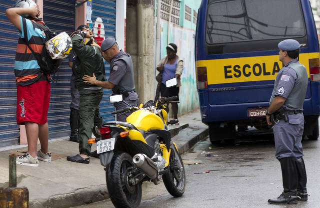 Military police frisk motorcyclists as they patrol in the Paraisopolis slum in Sao Paulo, Brazil, early Tuesday, Nov. 13, 2012. At least 140 people have been murdered in South America's biggest city over the past two weeks in a rising wave of violence, Sao Paulo's Public Safety Department said Sunday. (AP Photo/Andre Penner)