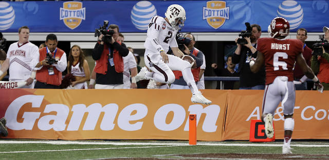 Texas A&M's Johnny Manziel (2) leaps into the end zone for a touchdown in front of Oklahoma's Demontre Hurst (6) during the college football Cotton Bowl game between the University of Oklahoma Sooners (OU) and Texas A&M University Aggies (TXAM) at Cowboy's Stadium on Friday Jan. 4, 2013, in Arlington, Tx. Photo by Chris Landsberger, The Oklahoman