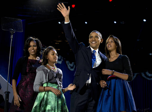 President Barack Obama waves as he walks on stage with first lady Michelle Obama and daughters Malia and Sasha at his election night party Wednesday, Nov. 7, 2012, in Chicago. Obama defeated Republican challenger former Massachusetts Gov. Mitt Romney. (AP Photo/Carolyn Kaster) ORG XMIT: ILCK101