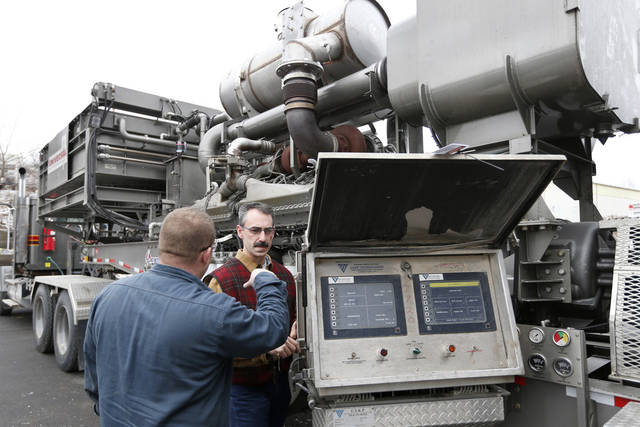 In this photo made on Thursday, Jan. 17, 2013, Universal Well Service fracturing engineering team leader Mike Michaelson, right, talks with technician Sean Cline  before they start the 16 cylinder diesel engine that has been converted to run on a blend of diesel and natural gas at the Cummins Bridgeway facility in Gibsonia, Pa. Oil- and gas-field companies from Pennsylvania to Texas are experimenting with converting the huge diesel engines that operate pumps that propel millions of gallons of water, sand and chemicals down a well bore in the fracturing process to break apart rock or tight sands that trap natural gas. (AP Photo/Keith Srakocic)