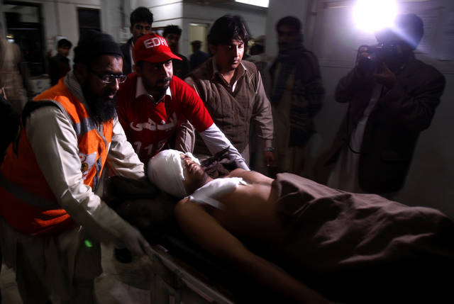 A Pakistani man who was injured in a suicide bombing is rushed by volunteers to a hospital in Peshawar, Pakistan, Friday, Feb. 1, 2013. A suicide bomber detonated his explosives outside a Shiite mosque in northwestern Pakistan as worshippers were leaving Friday prayers, killing several people and wounding dozens in the latest apparent sectarian attack in the country, police said.(AP Photo/Mohammad Sajjad)