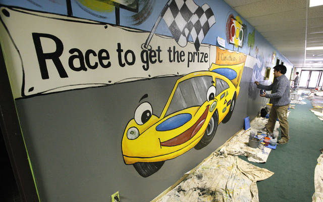 Artists with Palmer Studios work on a racetrack-themed mural in the children&acirc;s ministry area at Oakcrest Church of Christ in south Oklahoma City.
