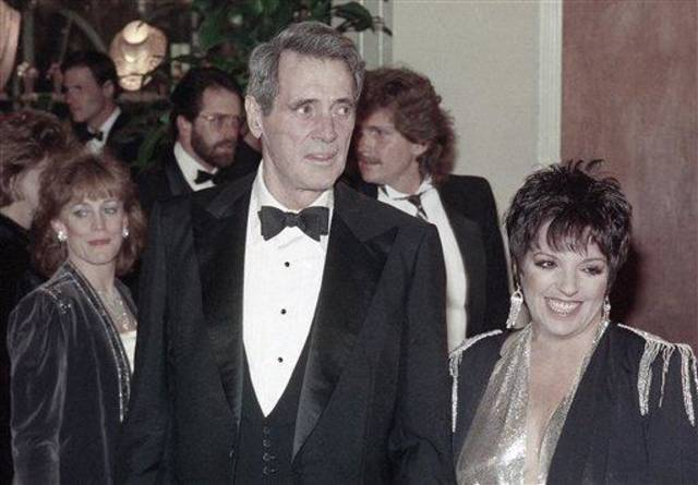 Liza Minnelli arrives with actor Rock Hudson on Jan. 26, 1985 at the 42nd annual Golden Globe Awards at Beverly Hilton Hotel in California.  Both are scheduled to present awards at the ceremony.  (AP Photo/Lennox McLendon)