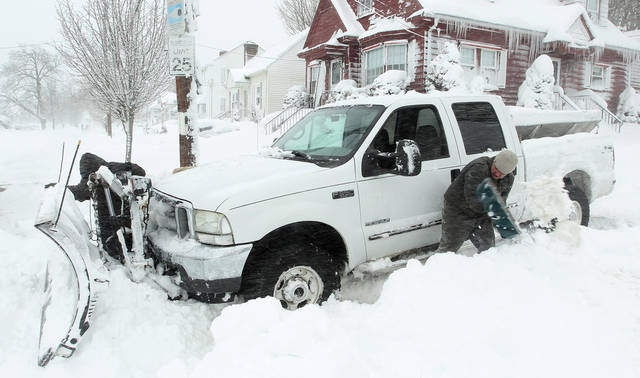 Michael Gelardi, right, and Larry Rose, left, attempt to dig out their snow plow after it got stuck in deep snow Saturday, Feb. 9, 2013, in Providence, R.I.  A howling storm across the Northeast left the New York-to-Boston corridor shrouded in 1 to 3 feet of snow Saturday, stranding motorists on highways overnight and piling up drifts so high that some homeowners couldn't get their doors open. More than 650,000 homes and businesses were left without electricity.(AP Photo/Stew Milne)