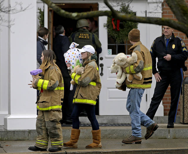 People carry stuffed animals as they pass officials entering the St. Rose of Lima Roman Catholic Church while responding to a bomb threat, Sunday, Dec. 16, 2012, in Newtown, Conn. Someone phoned in a threat as parishioners remembered 20 children and six adults who were massacred at an elementary school, but police later said nothing dangerous was found. At least a dozen police in camouflage SWAT gear and carrying guns soon arrived. (AP Photo/David Goldman)  ORG XMIT: CTDG120