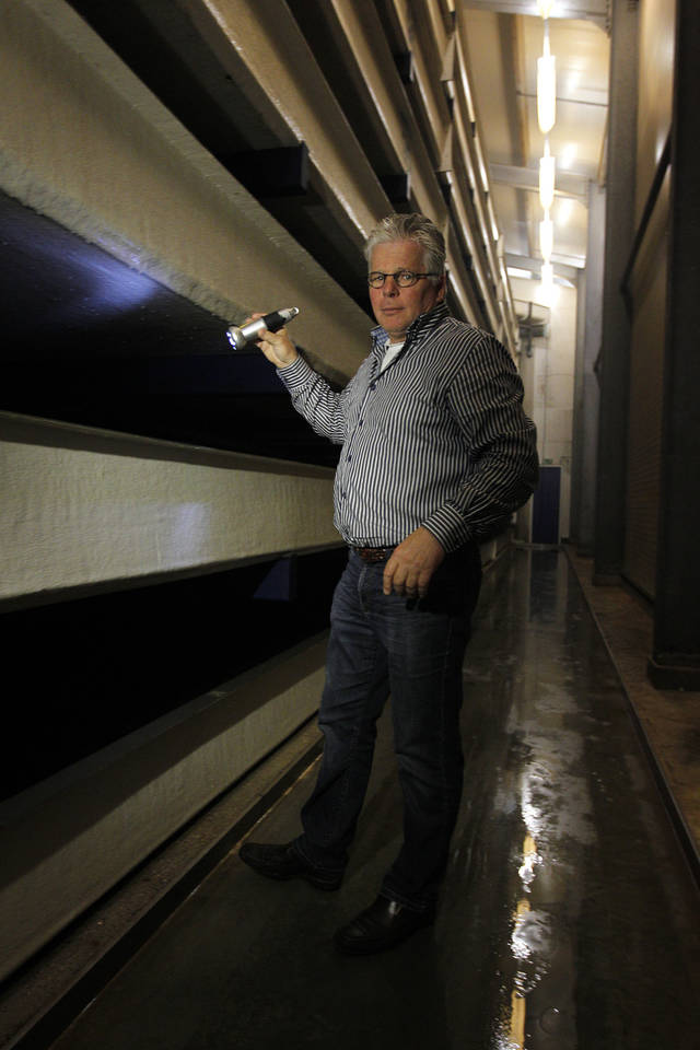 Adri Bout shines a light as he inspects turbot swimming in a tank at Seafarm, a fish farm in Kamperland, southern Netherlands, Tuesday, Aug. 23, 2011, where owner Adri Bout is trying new ways to solve common problems like disease control and waste disposal. Bout designed an eight-story high-rise tank where he raises 100 tons of turbot a year, in water which is kept cool enough so bacteria does not spread and using gravity to circulate the water. Forget about the romance of fishermen braving rough seas to bring home their catch, sustainability is a growing issue in aquaculture which now provides half the world's sea food. (AP Photos/Bas Czerwinski)