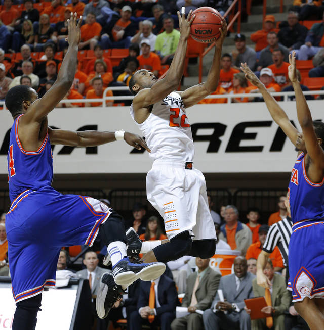 Oklahoma State's Markel Brown goes between Texas-Arlington's Kevin Butler, left, and Jamel Outler during a college basketball game between Oklahoma State University and UT Arlington at Gallagher-Iba Arena in Stillwater, Okla., Wednesday, Dec. 19, 2012. Photo by Bryan Terry, The Oklahoman3