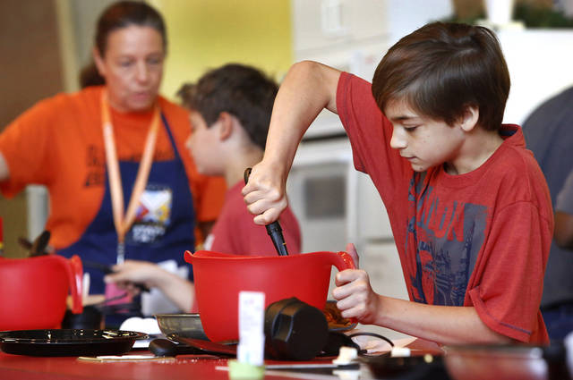Zachary Jenkins, 11, stirs batter for his pumpkin spice pancakes while competing in the Shawnee Mills&#039;  Kids&#039; Pancakes, Flapjacks and Griddle Cakes Contest at the Oklahoma State Fair on Saturday, Sep. 22, 2012. The event was held in the Creative Arts Building. Jenkins lives in Newalla and is a 6th grade home-schooled student.   Photo by Jim Beckel, The Oklahoman.