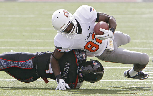 Oklahoma State Cowboys wide receiver Isaiah Anderson (82) is brought down by Texas Tech Red Raiders cornerback Derrick Mays (4) during the college football game between the Oklahoma State University Cowboys (OSU) and Texas Tech University Red Raiders (TTU) at Jones AT&amp;T Stadium on Saturday, Nov. 12, 2011. in Lubbock, Texas.  Photo by Chris Landsberger, The Oklahoman  ORG XMIT: KOD