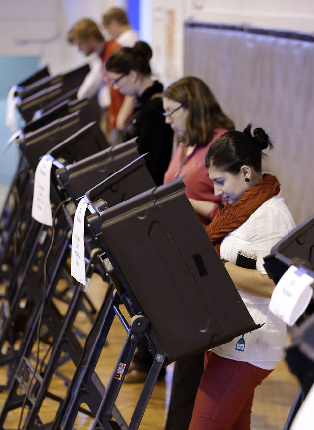 Marie Vazquez, right, votes at West End Middle School on election day on Tuesday, Nov. 6, 2012, in Nashville, Tenn. After a grinding presidential campaign, Americans are heading into polling places across the country.(AP Photo/Mark Humphrey)