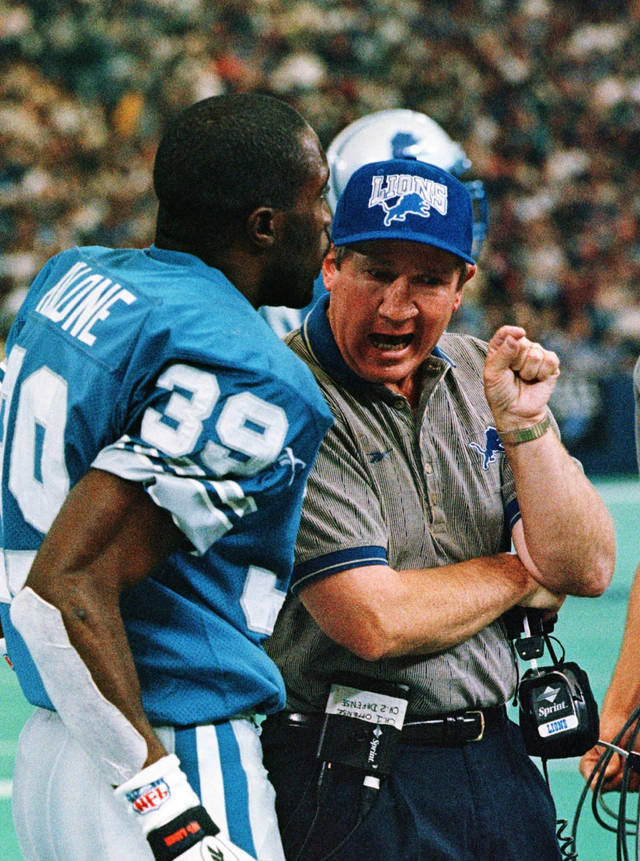 Former Lions coach Bobby Ross, right, talks with Detroit safety Van Malone during a 1997 game. Malone was drafted by Detroit after a standout career at TexasAP photo