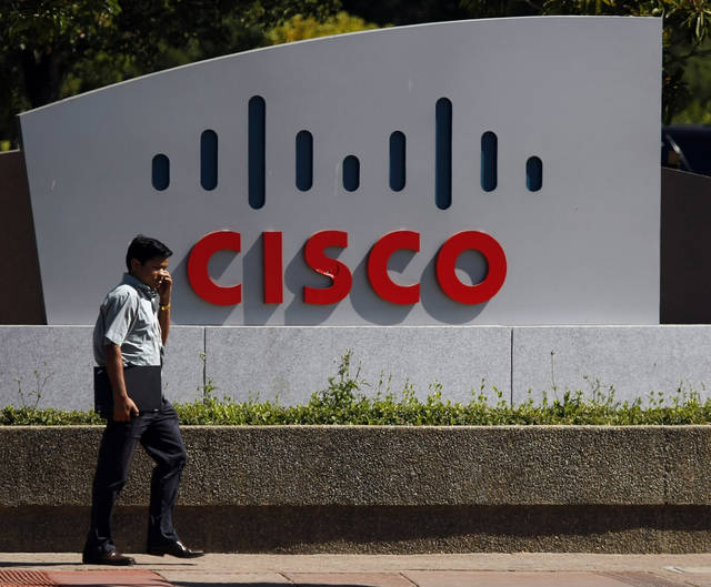 FILE - In this Aug. 9, 2010 file photo, a pedestrian walks by a Cisco sign outside of the office headquarters in San Jose, Calif. Cisco Systems Inc. releases financial results for the last quarter of 2012 on Wednesday, Feb. 13, 2013, after the market closes. (AP Photo/Marcio Jose Sanchez, File)