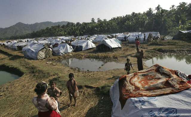 In this photo taken on Nov. 10, 2012, Muslim refugees stand near their tent at Sin Thet Maw relief camp in Pauktaw township, Rakhine state, western Myanmar. Myanmar�s government has launched a major operation aimed at verifying the citizenship of Muslims in western Rakhine state, the coastal territory that has been torn apart by Buddhist-Muslim violence since June.  Questions over whether the region's Muslim Rohingya population qualify for citizenship are at the heart of a crisis that has killed nearly 200 people and displaced 110,000 more.    (AP Photo/Khin Maung Win)