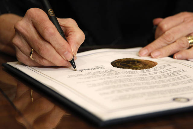 Gov. Chris Gregoire signs Referendum 74, a citizen-passed measure that legalizes same-sex marriage in the state, Wednesday, Dec. 5, 2012, in Olympia, Wash. Gregoire and Reed both signed the document at the ceremony, which allows gay couples to marry beginning Dec. 9. (AP Photo/Elaine Thompson)
