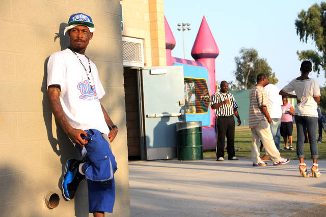 In this Wed. July 6,2011 photo, Eric Romero, also known as Lil Drawz, waits outside the gym at the Imperial Courts housing project. The gym and recreation center are taking part in the Summer Night Lights gang violence reduction program. (AP Photo/Thomas Watkins)