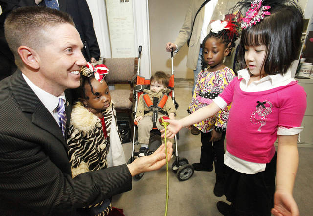 Senator Josh Brecheen gets a rose from Bria Basinger, 6, of Edmond during Rose Day at the state Capitol, Wednesday, February 8, 2012.  With Bria are her adopted siblings Aven, 2, Karston, 1, and Abree,6.  Photo by David McDaniel, The Oklahoman