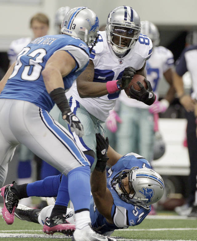 Dallas Cowboys wide receiver Dez Bryant takes the ball down field as Detroit Lions defensive end Kyle Vanden Bosch, left, and DeAndre Levy bottom defend during the first quarter of an NFL football game Sunday, Oct. 2, 2011, in Arlington, Texas. (AP Photo/Tony Gutierrez)