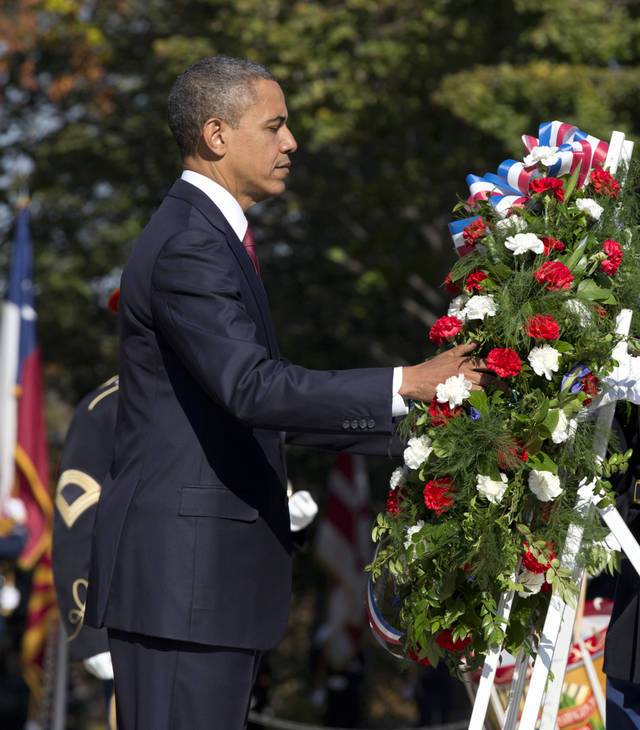 President Barack Obama presents a wreath at the Tomb of the Unknowns at Arlington National Cemetery during a Veterans Day ceremony in Arlington, Va., Sunday, Nov. 11, 2012. (AP Photo/J. Scott Applewhite)