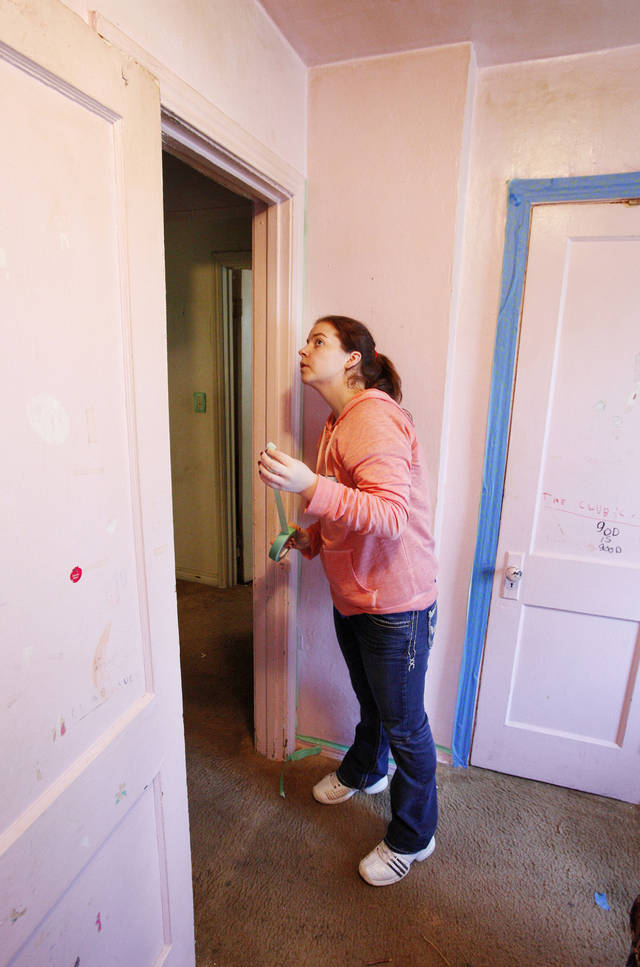 Casady High School junior Katie Hanstein, 17, prepares a door for painting.