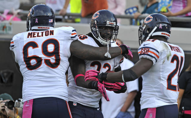 Chicago Bears cornerback Charles Tillman, center, celebrates with teammates defensive tackle Henry Melton (69) and strong safety Major Wright (21) after intercepting a pass and scoring a 36-yard touchdown against the Jacksonville Jaguars during the second half of an NFL football game, Sunday, Oct. 7, 2012, in Jacksonville, Fla. (AP Photo/Stephen Morton)