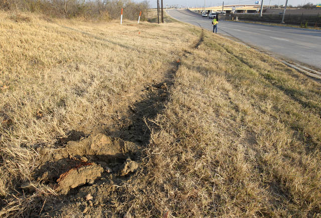 Tire ruts are seen on the ground with skid marks, at rear on road, at the site of single vehicle accident involving Dallas Cowboys player Josh Brent as a news cameraman, rear, films the area, Saturday, Dec. 8, 2012, in Irving, Texas. Brent is facing an intoxication manslaughter charge after a one-vehicle accident that killed linebacker Jerry Brown, a member of the team's practice squad. (AP Photo/Tony Gutierrez)