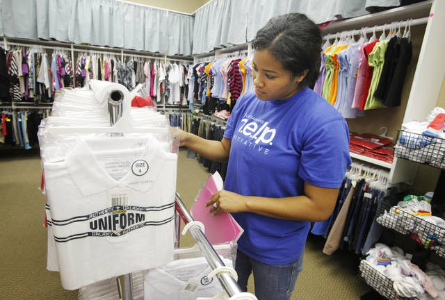 Volunteer Janelle Montgomery, from Okla. City, helping a foster child pick out a school uniform at Citizens Caring for Children in Oklahoma City Monday, July 23, 2012.  Photo by Paul B. Southerland, The Oklahoman