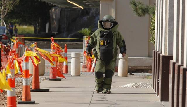 Oklahoma City Police Department bomb squad member on the sidewalk in front of the IRS building, 55 N Robinson, using video to look at a suspicious package left next to a mail box. Photo by Paul Southerland.
