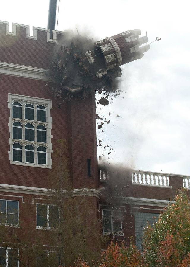 A turret crashes from the side of Benedictine Hall at St. Gregory�s University after it was pushed down for safety reasons following the Nov. 5, 2011, earthquake that damaged the building. Photo provided