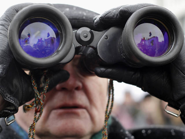 An elderly protester looks through the binoculars during a protest against alleged vote rigging in Russia's parliamentary elections on Sakharov avenue in Moscow, Russia, Saturday, Dec. 24, 2011. Tens of thousands of demonstrators on Saturday cheered opposition leaders and jeered the Kremlin in the largest protest in the Russian capital so far against election fraud, signaling growing outrage over Prime Minister Vladimir Putin's 12-year rule. (AP Photo/Ivan Sekretarev)