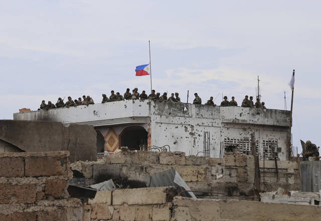 The Philippine national flag flies at half-staff as soldiers watch a news conference below of top Government officials at the site of a three-week intense fighting between Government forces and Muslim rebels who have taken nearly 200 people hostages, in Zamboanga city, southern Philippines, Saturday Sept. 28, 2013. The deadly standoff between government troops and Muslim rebels has ended with all of the captives safe, officials said Saturday. Defense Secretary Voltaire Gazmin said only a handful of Moro National Liberation Front rebels remained in hiding and were being hunted by troops in the coastal outskirts of the city, adding authorities were trying to determine if rebel commander Habier Malik, who led the Sept. 9 siege, was dead. More than 200 people were killed in the clashes, including 183 rebels and 23 soldiers and police, in one of the bloodiest and longest-running attacks by a Muslim group in the south, scene of decades-long Muslim rebellion for self-rule in the largely Roman Catholic country. (AP Photo)