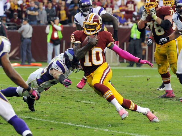 Washington Redskins quarterback Robert Griffin III (10) gets away from Minnesota Vikings safety Harrison Smith (22) to score a touchdown during the first half of an NFL football game, Sunday, Oct. 14, 2012, in Landover, Md. (AP Photo/Richard Lipski)