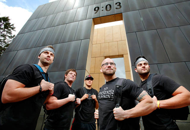 These five men will participate in Sunday's Memorial Marathon carrying 168 pounds that will be distributed among their backpacks, symbolizing the 168 people who were killed in the bombing of the Oklahoma City Alfred P. Murrah Federal Building in 1995.  Posing with the west wall of the Memorial as a backdrop are, from left, Jake Adkins, Chris Murphy, John O'Toole, Sean Shearon and Eric Stanley on Wednesday, April 27, 2011  Photo by Jim Beckel, The Oklahoman