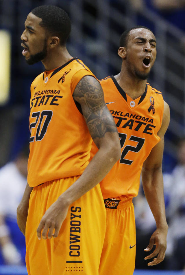 Oklahoma State guard Markel Brown (22) and forward Michael Cobbins (20) celebrate a lead during the second half of an NCAA college basketball game against Kansas in Lawrence, Kan., Saturday, Feb. 2, 2013. Oklahoma State won 85-80. (AP Photo/Orlin Wagner) ORG XMIT: KSOW108